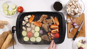 Cook hands turning the meat on the grill alongside to vegetables. Top view of cook hands turning the meat on the grill alongside to vegetables that are cooked stock footage