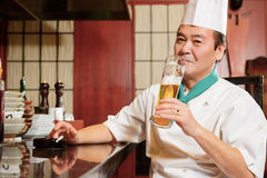 Cook has a drink in restaurant kitchen Royalty Free Stock Photos