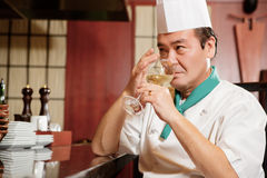 Cook has a drink in restaurant kitchen Royalty Free Stock Photography