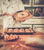 Cook holding baked goods Royalty Free Stock Image