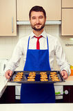 Cook holding baking tray with cookies Royalty Free Stock Photography