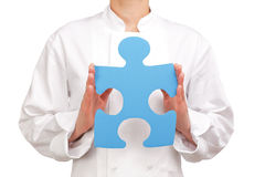 Cook holding a blue puzzle piece Royalty Free Stock Photos