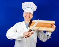 Cook holding cutting board and knives Royalty Free Stock Image