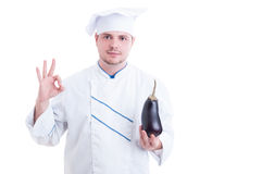 Cook holding eggplant and showing like or thumb-up Stock Photography