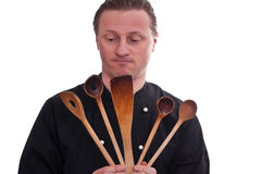 Cook is holding five cooking spoons Stock Image