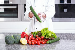 Cook holding in the hands of cucumber Royalty Free Stock Photo