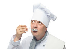 Cook holding a spoon in his hand and trying to taste Royalty Free Stock Photos