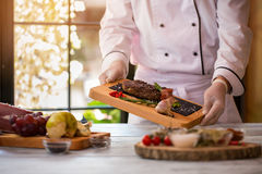 Cook holds board with meat. Stock Image