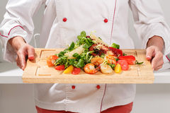 Cook holds a cutting board with salad Stock Image