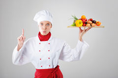 Cook holds in one hand a tray. Cook with mountain prohibited vegetables Stock Photos
