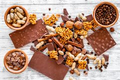 Cook homemade chocolate. Chocolate bars, nuts, sugar, coffee beans, cinnamon on grey wooden background top view.  Stock Images