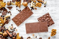 Cook homemade chocolate. Chocolate bars, nuts, sugar, coffee beans, cinnamon on grey wooden background top view.  Stock Photo