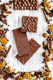 Cook homemade chocolate. Chocolate bars, nuts, sugar, coffee beans, cinnamon on grey wooden background top view.  Stock Photos