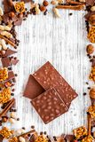 Cook homemade chocolate. Chocolate bars, nuts, sugar, coffee beans, cinnamon on grey wooden background top view.  Royalty Free Stock Image