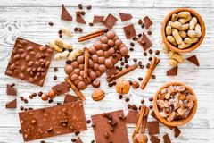 Cook homemade chocolate. Chocolate bars, nuts, sugar, coffee beans, cinnamon on grey wooden background top view Royalty Free Stock Photography