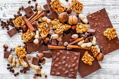 Cook homemade chocolate. Chocolate bars, nuts, sugar, coffee beans, cinnamon on grey wooden background top view Royalty Free Stock Photos