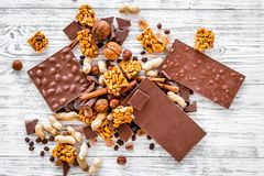 Cook homemade chocolate. Chocolate bars, nuts, sugar, coffee beans, cinnamon on grey wooden background top view.  Royalty Free Stock Photo