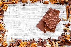 Cook homemade chocolate. Chocolate bars, nuts, sugar, coffee beans, cinnamon on grey wooden background top view Stock Image