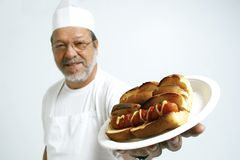 Cook with hot dogs. Cook offering two mustard and ketchup hot dogs Royalty Free Stock Photo