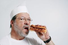 Cook is hungry. He's tasting his hot dog Stock Photography