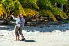 COOK ISLAND, SOUTH PACIFIC - SEPTEMBER 30, 2018: Couple making selfie on a sandy beach. Copy space for text royalty free stock images