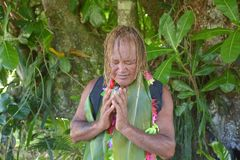 Cook Islander blessing on Noni Juice during Eco tourism tour in. Cook Islander Pa blesses on noni juice during an Eco tourism tour in Rarotonga Cook Islands royalty free stock photography