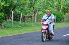 Cook Islander woman rids motorbike. AITUTAKI - SEP 18 2013:Cook Islander woman rids motorbike. Aitutaki is the second most visited island of the Cook Islands.It Stock Image