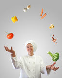 Cook juggler. Woman cook juggler with vegetables and other food ingredients Stock Photo