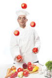 Cook juggles vegetables. Over white Stock Photography