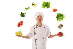Cook juggling with fresh vegetables Royalty Free Stock Photography