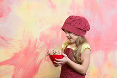 Cook kid in chef hat, apron hold cookies or biscuits Royalty Free Stock Photos
