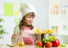 Cook kid makes healthy vegetables meal in the. Cook kid girl makes healthy vegetables meal in the kitchen Stock Images