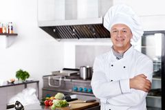 Cook in the kitchen. Mature cook in the kitchen Royalty Free Stock Photo