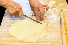 Cook in kitchen cuts pastry from dough Stock Photos