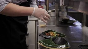 The cook in the kitchen decorates the dish with greens in a plate. stock footage