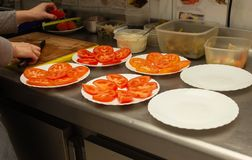 The cook in the kitchen prepares salads with tomato and smoothes it in portions, close-up, restaurant. The cook in the kitchen prepares salads with tomato and stock images