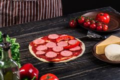 Cook in the kitchen putting the ingredients on the pizza. Pizza concept. Production and delivery of food. Cook in the kitchen putting the ingredients on the Royalty Free Stock Photo