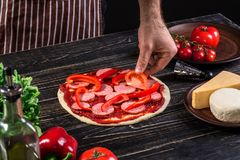 Cook in the kitchen putting the ingredients on the pizza. Pizza concept. Production and delivery of food. Cook in the kitchen putting the ingredients on the Stock Photo