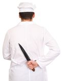 Cook with a knife. Cook in a white dressing-gown holding in a hand kitchen knife Royalty Free Stock Photography