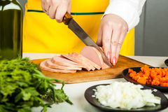 Cook knife cuts sausage Royalty Free Stock Photography