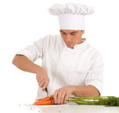 Cook with knife cutting bunch of carrots Stock Photo
