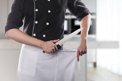 Cook with knife, front view with kitchen on background. 3D rendering and photo. High resolution. Royalty Free Stock Photos