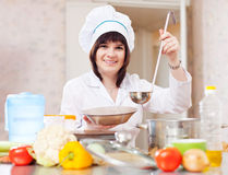 Cook with ladle pours soup to plate Royalty Free Stock Images