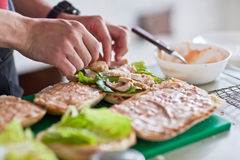 Cook lays out the pieces of herbs and chicken on toast for a panini Royalty Free Stock Photo