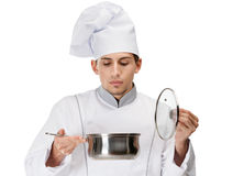 Cook looking into stew pan Royalty Free Stock Images