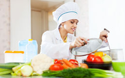 Cook  looks into the saucepan in  kitchen Royalty Free Stock Photography