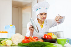 Cook looks into  saucepan in kitchen Royalty Free Stock Images