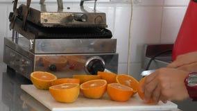 Cook lub barman tnące pomarańcze dla soku zdjęcie wideo