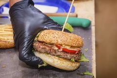 Cook made a hamburger and gave it to the buyer. Cooking food on the street. Close-up stock images