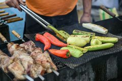 Cook makes grilled vegetables and meat on a street food festival Stock Photos
